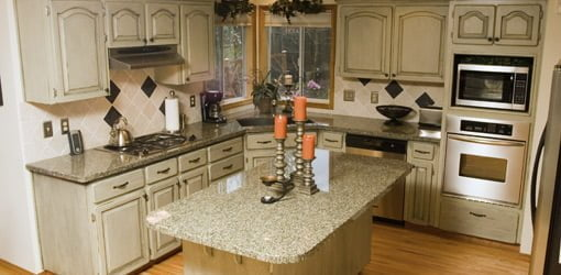 Green kitchen with granite countertops.