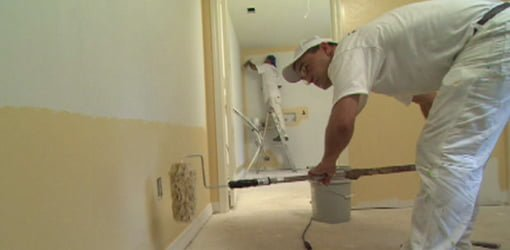 Painter rolling walls in room.