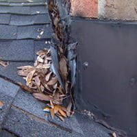 Flashing pulled away from chimney with leaves behind it.