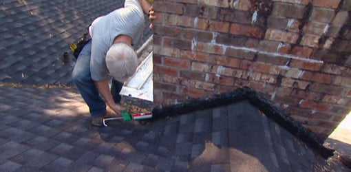 Applying Roofing Cement To Flashing Around Chimney.