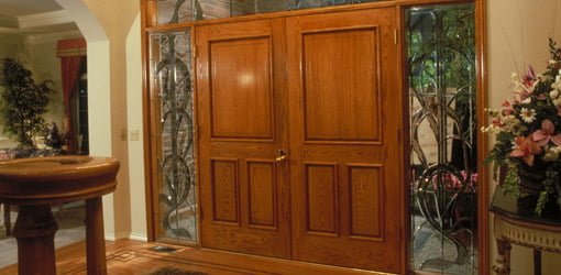 Wood double entry doors with leaded glass sidelights.