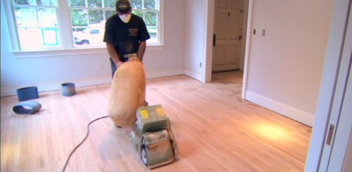 Sanding hardwood floor with drum sander.