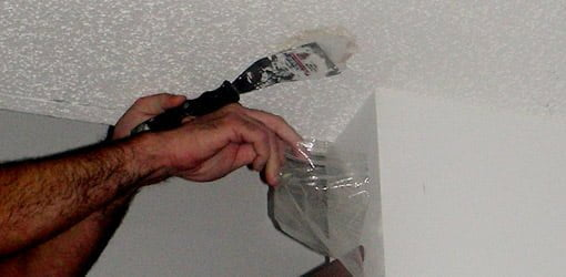 Obtaining a sample of ceiling texture to test for asbestos