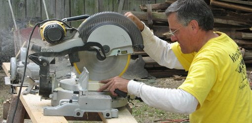 Motorized miter saws being used to crosscut wood stock.