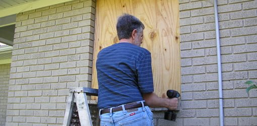 Using a cordless drill to attach plywood to a window