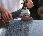 Using grinder to polish granite.