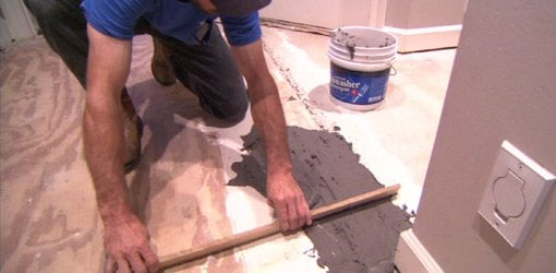 Using floor patching compound to level a subfloor.