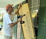 installing wooden panels to protect windows from wind