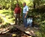 Allen and Danny standing on a bridge over a pond