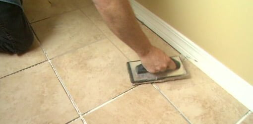 Applying grout to a tile floor.