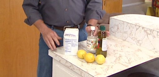 Baking soda, vinegar, olive oil, and lemons on kitchen counter.