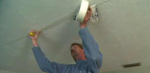 Drywall finisher applying drywall tape to a ceiling crack.