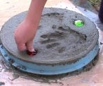 Pressing colored rocks into personalized stepping stone.