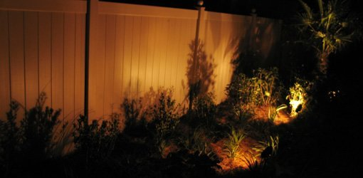 Fence At Night Lit By Landscape Lights.