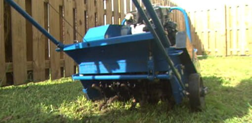 Using a self propelled, gas powered, walk behind aerator to aerate a lawn.