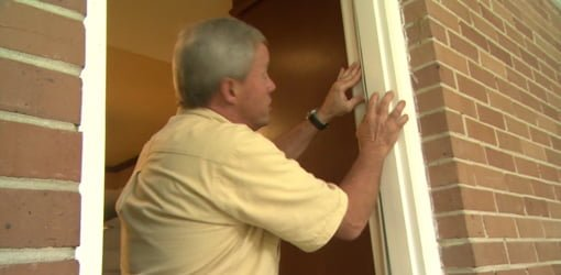 Danny Lipford replacing weatherstripping on side of door frame.
