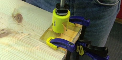 Drilling hole with plywood scraps clamped to stock