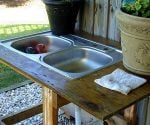 Outdoor utility sink made from old kitchen sink, plywood top, and wood base
