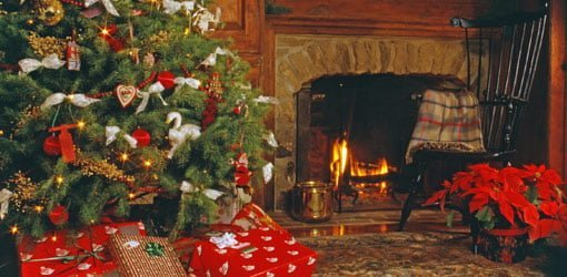 Christmas tree with gifts next to fireplace