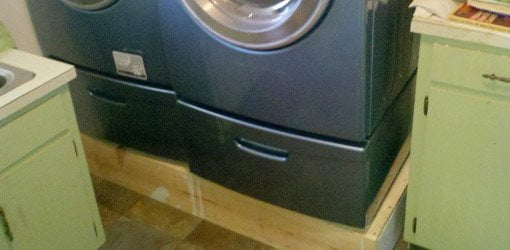 Wood platform under clothes washer and dryer
