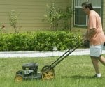 Man cutting lawn in front of house.