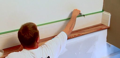 Using putty knife to press down painter's tape
