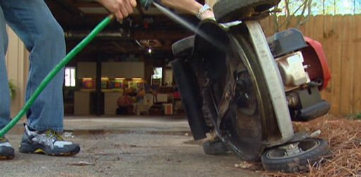 Cleaning the underside of a lawn mower with a garden hose