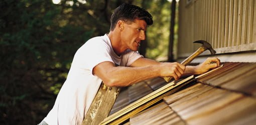 Roofer roofing house with wood shingles.