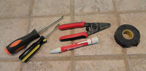 Screwdrivers, wire strippers, voltage tester, and electrical tape
