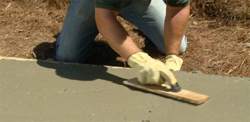 Using a wood float to smooth surface of concrete slab