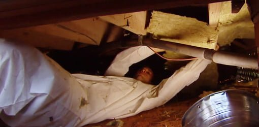 Man in white jumpsuit adding insulation between joists in crawlspace under house.