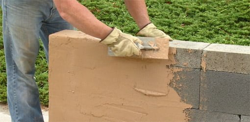 Applying surface bonding cement to concrete block wall