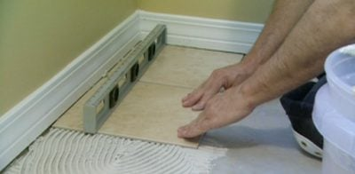Using level to install tile on floor.