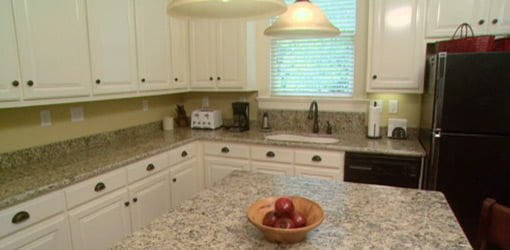 Remodeled kitchen with white painted cabinets and granite countertops.