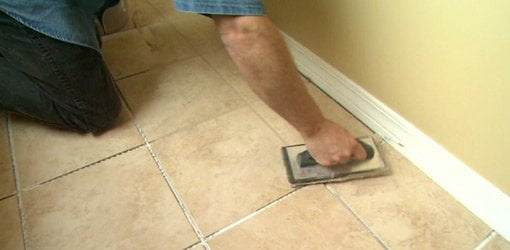 Putting grout on a tile floor.