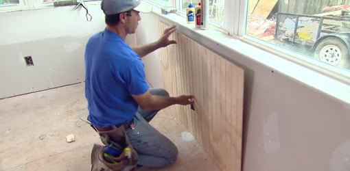 Installing beadboard paneling on sunroom walls.