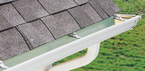 White aluminum gutter on house with gray shingle roof.