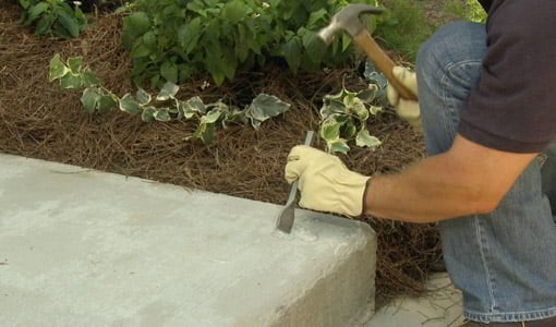 Removing damaged concrete with hammer and chisel.