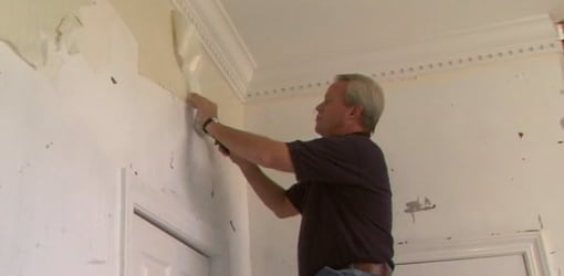 Danny Lipford stripping wallpaper from wall.