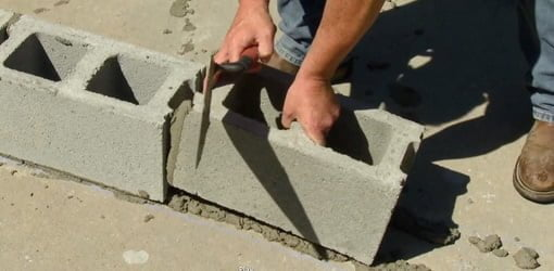 Laying concrete blocks for a wall.