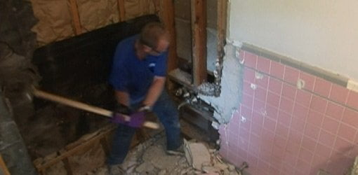 Knocking tile off wall with sledgehammer.