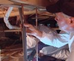 Danny Lipford installing foam insulation on water pipe in crawlspace under house.