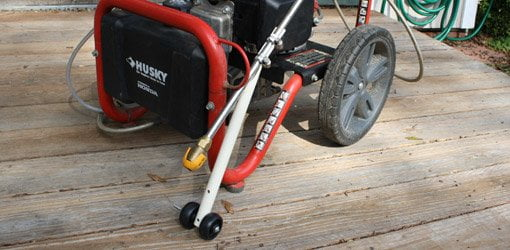 Pressure washer wand roller guide made from PVC pipe and casters.