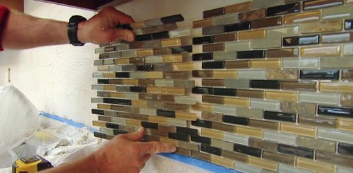 installing a sheet of mosaic tile on a kitchen backsplash