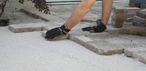 Laying Pavers On A Base Of Crushed Limestone Topped With Sand.