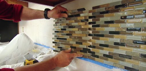 Installing a DIY mosaic glass tile backsplash in a kitchen.