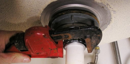 using a pipe wrench to unscrew the nut holding the drain pipe tailpiece - Kitchen Sink Wrench