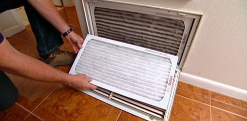 Changing an air conditioner air filter.