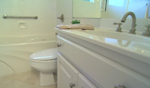 Clean lines of white painted bathroom vanity with molded cultured marble top and sink.