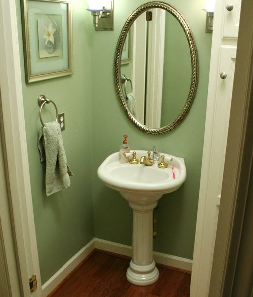 Pedestal sink with green walls.